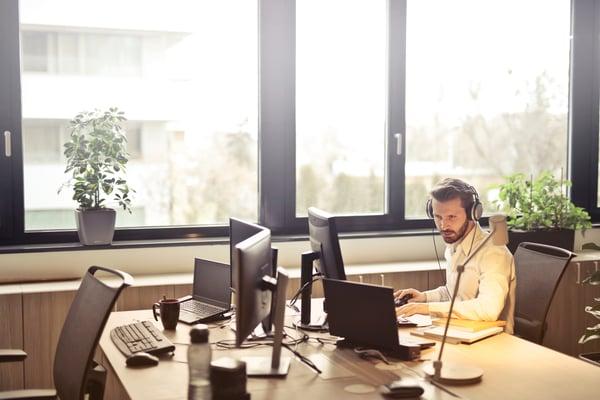man-with-headphones-facing-computer-monitor-845451